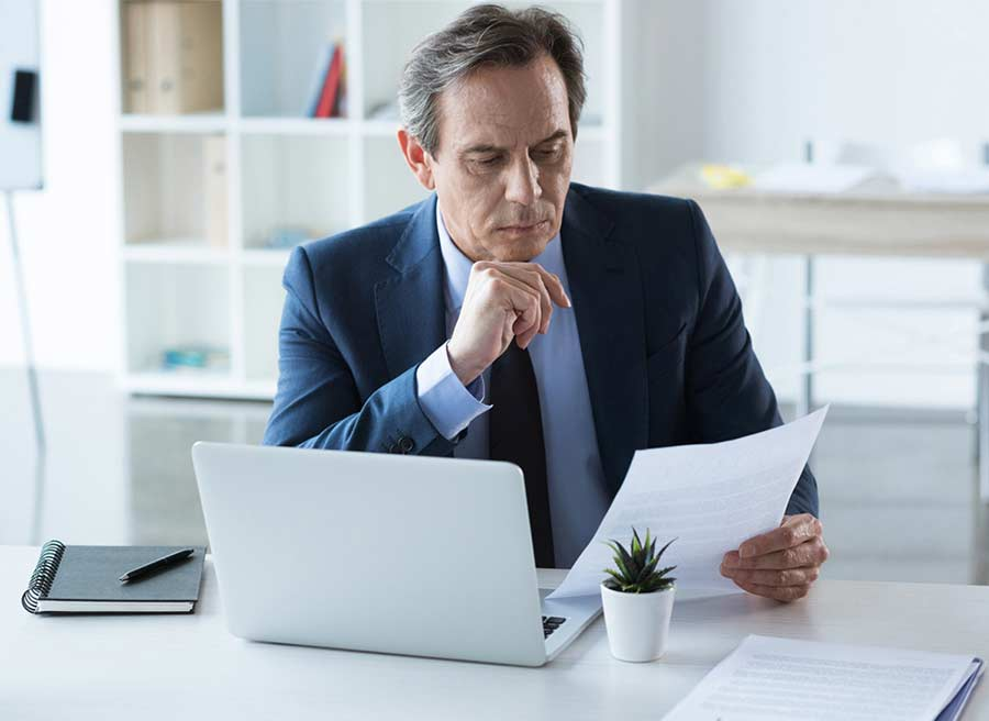 man with laptop examining documents