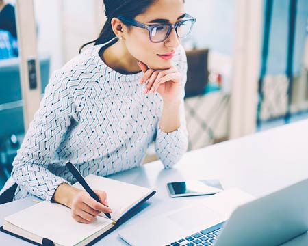 Woman in a pony tail wearing glasses looking at a laptop and taking notes