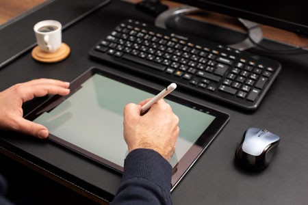 Hand using a digital pen on a tablet