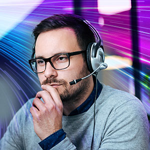 Man with headset and glasses rests chin on hand