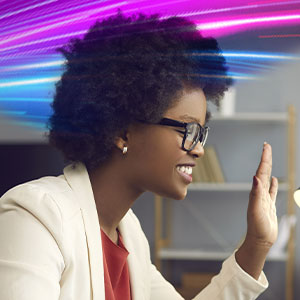 Woman with glasses waving at a computer screen