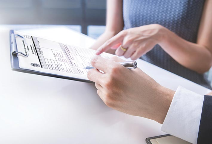 Photo of a man and woman's hands filling out a form on a clipboard