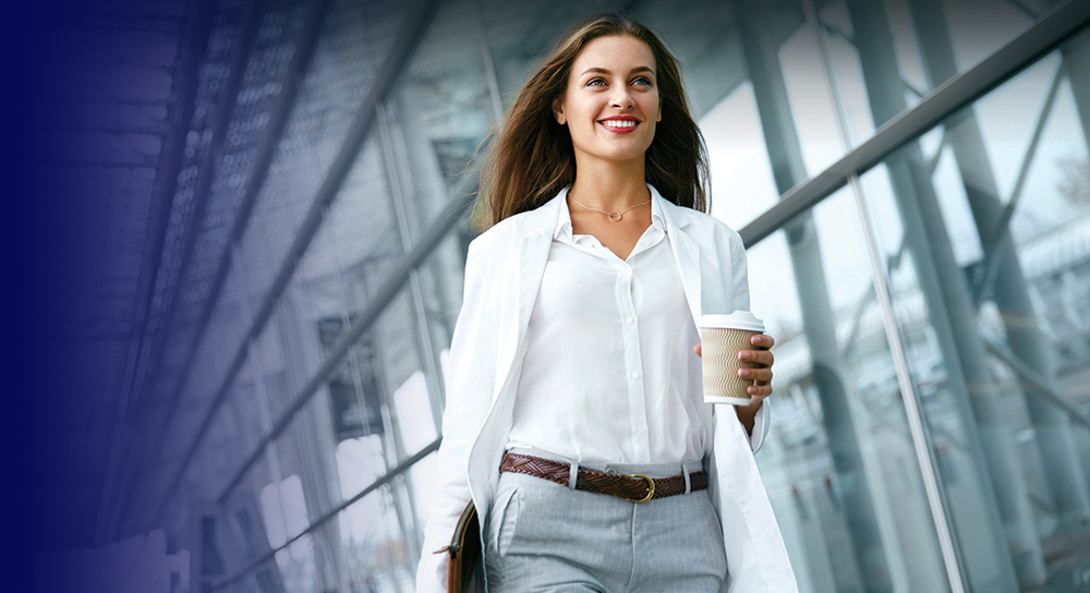 woman with long brown hair wearing a white shirt and coat carrying a cup of coffee walking confidently