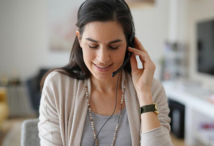 woman on a headset looking down and smiling