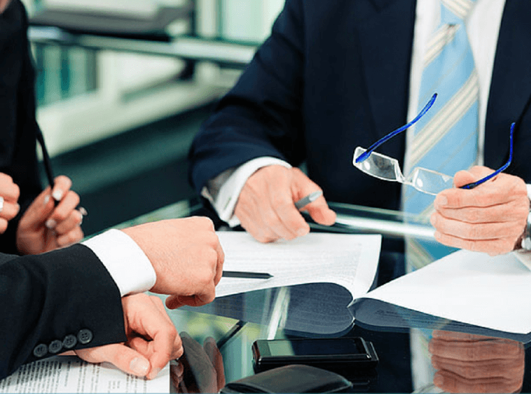 Two people in suits reviewing a document