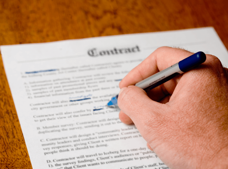 Hand holding a pen and marking a document