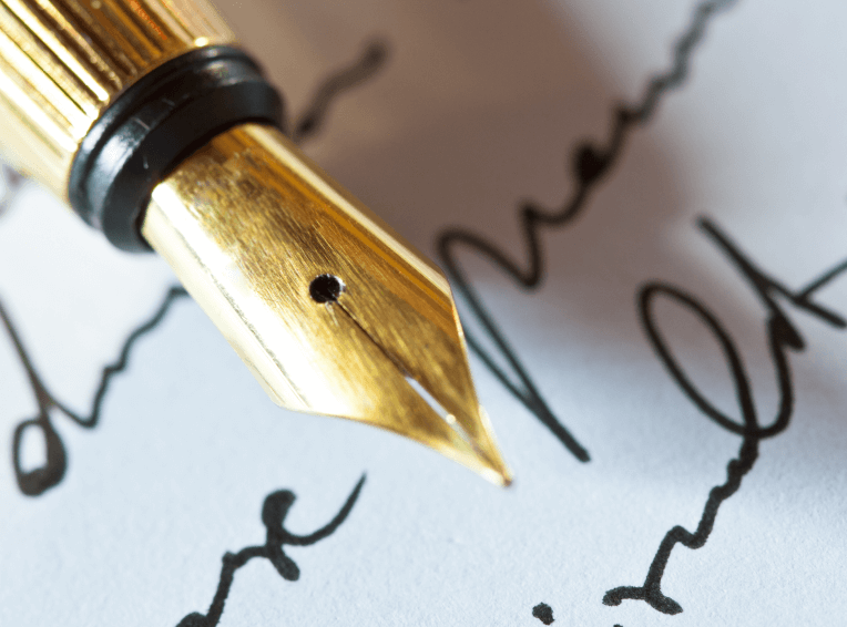 Close-up of a gold pen on top of cursive writing