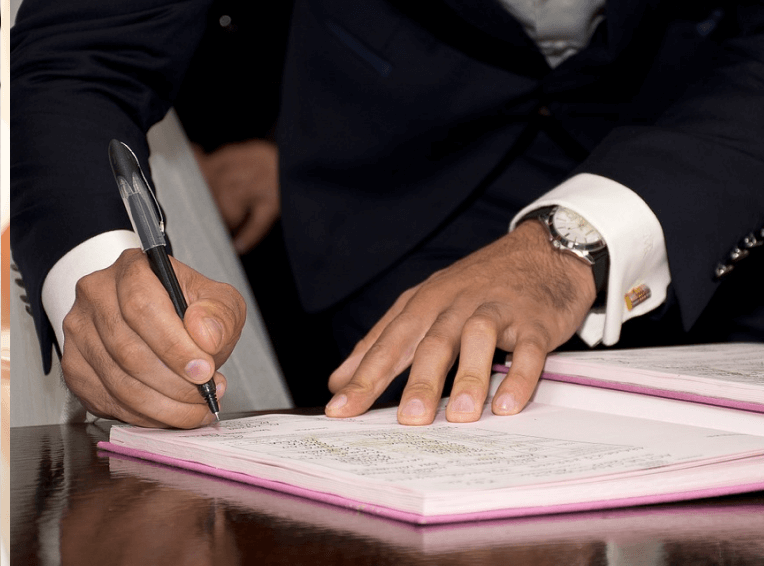 Hand with a pen signing a document