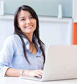 Woman with long dark hair in front of a laptop looking at the camera and smiling