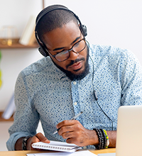 Black man with a mustache and beard wearing headphones and glasses taking notes